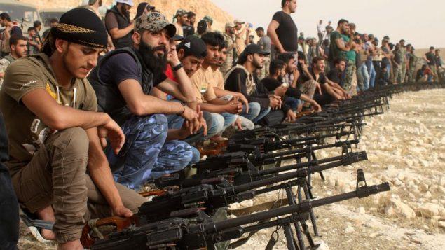 مقاتلو معارضة سوريون يجلسون خلف رشاشات خلال موكب عسكري بالقرب من مدينة درعا جنوب سوريا، 7 يونيو 2018 (Mohamad Abazeed/AFP)