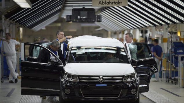 عمال شركة فولكسفاغن للسيارات يفحصون سيارة في مصنع الشركة في فولسبرغ، المانيا، 21 اكتوبر 2015 (ODD ANDERSEN / AFP)
