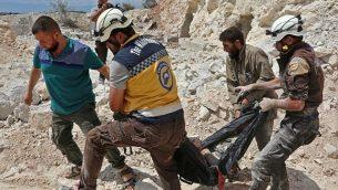 هذه الصورة تم التقاطها في كفر عين في 7 سبتمبر، 2018، وتظهر عناصر من منظمة 'الدفاع المدني السوري'، التي تُعرف أيضا بإسم 'الخوذ البيضاء', يحملون أحد الضحايا بعد غارات جوية، على بعد 4 كيلومترات شرقي خان شيخون في الريف الجنوبي من محافظة إدلب.  (AFP PHOTO / Anas AL-DYAB)