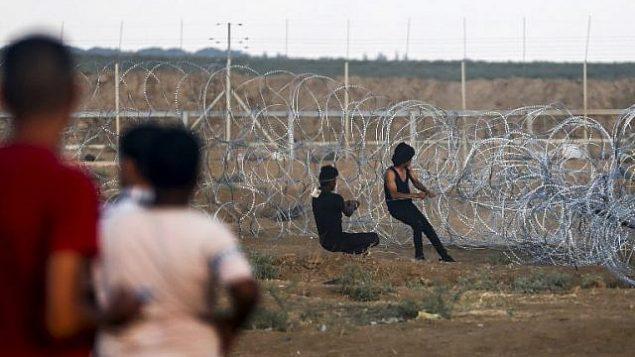 فلسطينيون يسحبون كابلا مربوطا بسياج شائك إثناء محاولتهم إسقاط قسم من السياج الأمني بين قطاع غزة وإسرائيل، خلال مواجهات على الحدود شرقي مدينة غزة، 7 سبتمبر، 2018.(AFP/Said Khatib)