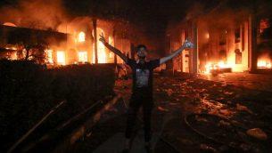 متاهر عراقي امام مبنى القنصلية الإيرانية في البصرة الذي تم احراقه خلال مظاهرات في المدينة، 7 سبتمبر 2018 (HAIDAR MOHAMMED ALI / AFP)