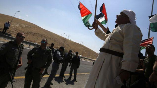 متظاهرون فلسطينيون يلوحون بالاعلام الوطنية امام جنود اسرائيليين خلال مظاهرة ضد هدم قرية خان الاحمر البدوية في الضفة الغربية، 14 سبتمبر 2018 (AFP PHOTO / ABBAS MOMANI)