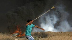 متظاهر فلسطيني يستخدم مقلاعا لإلقاء الحجارة باتجاه القوات الإسرائيلية التي أطلقت الغاز المسيل للدموع خلال مظاهرة على امتداد السياج الحدودي شرق مدينة غزة في 14 سبتمبر 2018. (AFP/Said Khatib)