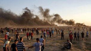 متظاهرون فلسطينيون يجتمعون أثناء مظاهرة على امتداد السياج الحدودي الإسرائيلي شرق مدينة غزة في 21 سبتمبر 2018 حيث تتصاعد أعمدة الدخان من الإطارات المحترقة في الخلفية. (AFP/Said Khatib)