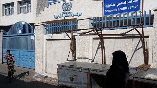 سيدة فلسطينية تمر من أمام مركز صحي مغلق تديره وكالة الأمم المتحدة لغوث وتشغيل اللاجئين (أونروا) خلال إضراب لكل مؤسسات الأونروا في رفح في جنوب قطاع غزة، 24 سبتمبر، 2018.  (AFP PHOTO / SAID KHATIB)