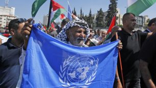 متظاهرون فلسطينيون يلوحون بعلم الأمم المتحدة والاعلام الفلسطينية امام بطاقة لاجئ ضخمة للرئيس الفلسطيني محمود عباس، خلال مظاهرة ضد قرار الولايات المتحدة في وقت سابق من العام وقف تمويل وكالة الامم المتحدة للفلسطينيين، في مدينة بيت لحم بالضفة الغربية، 26 سبتمبر 2018 (AFP/Musa Al SHAER)