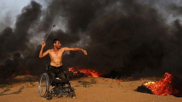 محتج فلسطيني على كرسي متحرك يلقي بالحجارة باتجاه القوات الإسرائيلية خلال اشتباكات على طول السياج الحدودي الإسرائيلي، شرق مدينة غزة في 28 سبتمبر 2018. (AFP PHOTO / Said KHATIB)