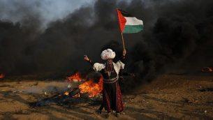 امرأة فلسطينية ترفع العلم أمام إطارات محترقة خلال اشتباكات على طول السياج الحدودي، شرق مدينة غزة في 28 سبتمبر 2018. ( AFP PHOTO / Said KHATIB)