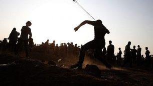 متظاهر فلسطيني يلقي حجرا  باتجاه القوات الإسرائيلية خلال مواجهات على السياج الحدودي، شرقي مدينة غزة في 28 سبتمبر، 2018. (AFP Photo/Said Khatib)