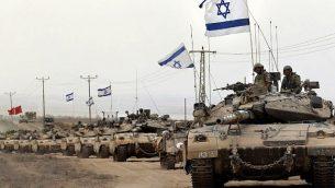 دبابات ميركافا الإسرائيلية تقترب من الحدود بين إسرائيل وقطاع غزة أثناء عودتها من القطاع الساحلي الفلسطيني الذي تسيطر عليه حماس في 5 أغسطس 2014، بعد أن أعلنت إسرائيل أن جميع قواتها قد انسحبت من قطاع غزة. (AFP/THOMAS COEX)