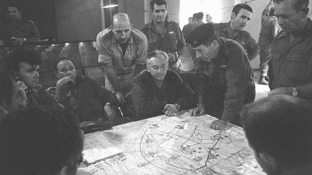 أعضاء هيئة الأركان العامة في الجيش الإسرائيلي ينظرون إلى خريطة أثناء اندلاع حرب أكتوبر في 7 أكتوبر 1973. (Bamahane/Defense Ministry Archives)