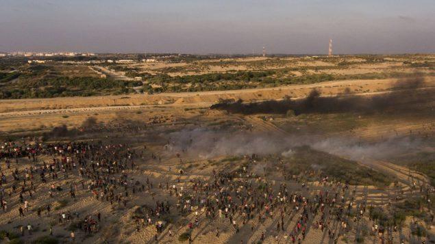 صورة جوية لمتظاهرين يفرون من الغاز المسيل للدموع الذي اطلقه جنود اسرائيليون خلال مظاهرة في شاطئ في بيت لاهيا، بالقرب من الحدود مع اسرائيل، 17 سبتمبر 2018 (AP/Felipe Dana)