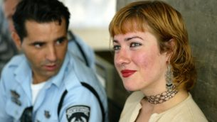 الصحفية المستقلة البريطانية والنشاطة ايوا جاويويك، الى جانب شرطي اسرائيلي قبل جلسة حول ترحيلها في محكمة تل ابيب المركزية، 18 اغسطس 2004 (AP Photo/Ariel Schalit)