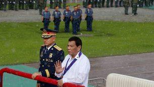 الرئيس دوتيرتي يطلب من حراس الأمن عدم تزويده بمظلة خلال استعراض للشرطة تحت أمطار مفاجئة في احتفالات بالذكرى ال117 لتأسيس خدمة الشرطة الوطنية في كامب كرامي في ضواحي مدينة كيزون، شمال شرق مانيلا، الفيليبين، 8 أغسطس، 2018، برفقته المفوض العام للشرطة الفيلبينية، أوسكار ألبيالدي. (AP Photo/Bullit Marquez)