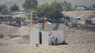 طفلات فلسطينيات يقفن إلى جانب حاوية شحن تم وضعها حديثا في قرية الخان الأحمر البدوية، 11 سبتمبر، 2018.   (AP Photo/Majdi Mohammed)