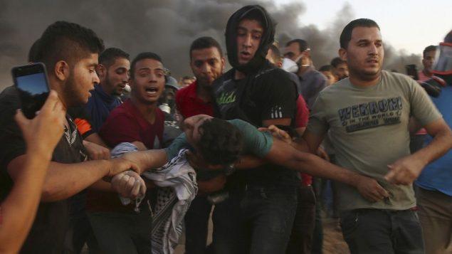 متظاهرون يخلون مراهقا اصيب بالقرب من الحدود بين قطاع غزة واسرائيل خلال مظاهرة، شرقي مدينة غزة، 14 سبتمبر 2018 (AP Photo/Adel Hana)