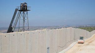 مركبة بناء إسرائيل تسير بجانب جدار إسمنتي يتم بناؤه على طول 'الخط الأزرق' الذي يفصل بين إسرائيل ولبنان، بينما يقف جنود في الجيش اللبناني في برج مراقبة من الطرف الثاني من الحدود، بالقرب من بلدة راس الناقورة الإسرائيلية، 5 سبتمبر، 2015.  (Judah Ari Gross/Times of Israel)