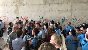 ناشطون يمينيون إسرائيليون يرتدون قمصانا زرقاء يتبادلون الهتافات مع نشطاء فلسطينيين وسكان محليين في ممر تحت الطريق السريع 1 بالقرب من قرية الخان الأحمر البدوية في الضفة الغربية، 7 سبتمبر / أيلول 2018. (لقطة شاشة: تويتر)