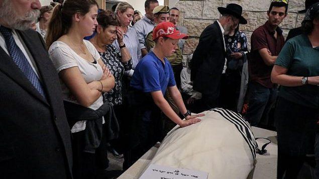 ابن آري فولد يضع يديه على جثمان والده خلال جنازته في كفار عتصيون في 17 سبتمبر، 2018. (Gershon Elinson/FLASH90)
