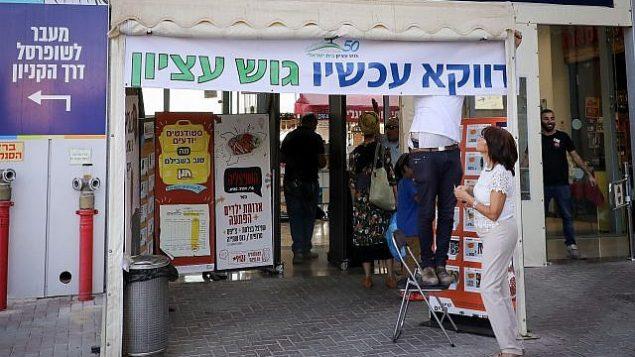 """في أعقاب هجوم بالقرب من مفترق غوش عتسيون، حيث قُتل رجل إسرائيلي يدعى آري فولد على يد مراهق فلسطيني، تم تعليق ملصقات تحمل اسم """"غوش عتسيون الآن"""" في المركز التجاري. 16 سبتمبر 2018. (Gershon Elinson/FLASH90)"""