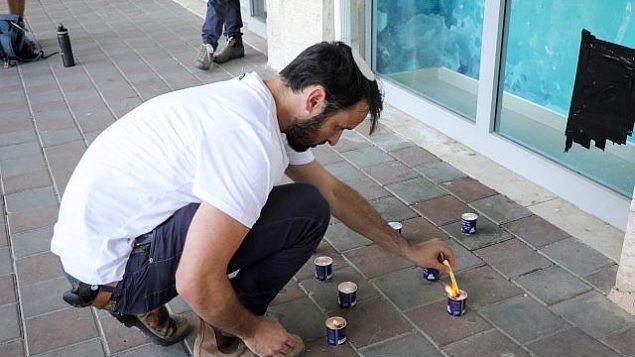 الناس يشعلون الشموع في ذكرى آري فولد، في الموقع الذي قُتل فيه في هجوم، في تقاطع غوش عتسيون، 16 سبتمبر 2018. (Gershon Elinson / FLASH90)