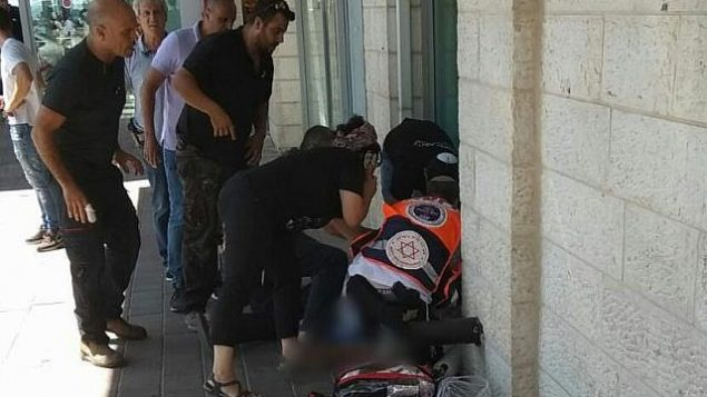 مسعفون يعالجون رجل اسرائيلي تعرض لهجوم طعن في مجمع تجاري بالقرب من مفرق كتلة عتصيون الاستيطانية، 16 سبتمبر 2018 (Magen David Adom)