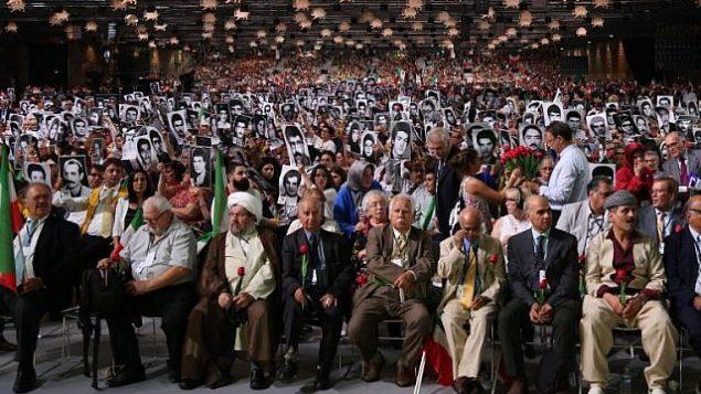 """اشخاص يحملون صورا لأقاربهم الذين قُتلوا بأيدي النظام الإيراني خلال حدث """"إيران حرة 2018 - البديل"""" في 30 يونيو، 2018، في فيلبانت، شمال فرنسا.  (AFP Photo/Zakaria Abdelkafi)"""