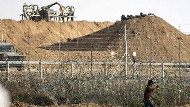 فلسطيني يستخدم مقلاع لرشق القوات الإسرائيلية في الطرف الاخر من الحدود بالحجارة خلال اشتباكات عند الحدود مع اسرائيل شرقي مدينة غزة، 13 يوليو 2018 (AFP PHOTO / MAHMUD HAMS)