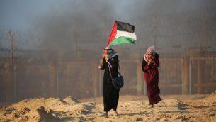 امرأة فلسطينية تحمل العلم الفلسطيني خلال مظاهرة من اجل رفع الحصار الإسرائيلي المفروض على قطاع غزة في شاطئ ببيت لاهيا، بالقرب من الحدود البحرية مع اسرائيل، 17 سبتمبر 2018 (AFP/Said Khatib)