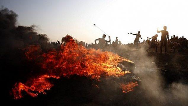 فلسطينيون يلقون الحجارة باتجاه القوات الإسرائيلية خلال مواجهات على الحدود بين إسرائيل وقطاع غزة، شرقي مدينة غزة، 28 سبتمبر، 2018. (AFP Photo/Said Khatib)