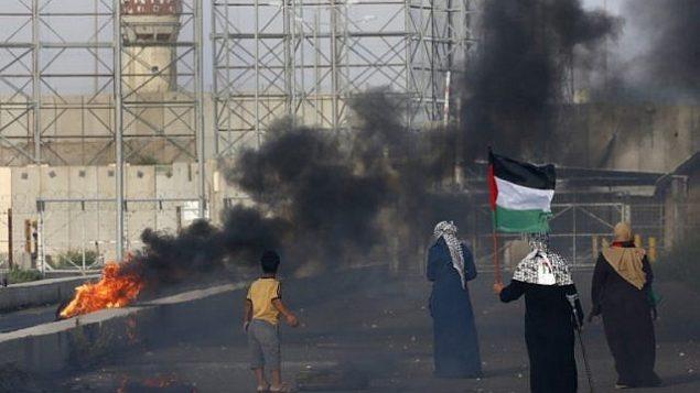 سيدة فلسطينية تحمل العلم الفلسطيني خلال مظاهرات عند معبر إيريز بين اسرائيل وشمال قطاع غزة، 3 اكتوبر 2018 (AFP/Said Khatib)