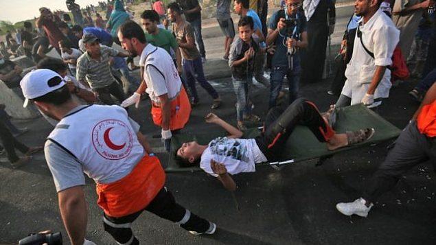 مسعفون فلسطينيون يحملون رجلا مصابا خلال مظاهرات عند معبر إيريز بين اسرائيل وشمال قطاع غزة، 3 اكتوبر 2018 (AFP/Said Khatib)