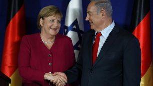 مصافحة بين رئيس الوزراء بينيامين نتنياهو والمستشارة الألمانية أنغيلا ميركل خلال خلال مؤتمر صحفي مشترك في 'فندق داوود' في القدس، 4 أكتوبر، 2018. (AFP Photo/Menahem Kahana)