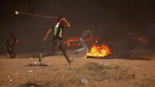 فلسطيني يرمي حجرا تجاه القوات الإسرائيلية خلال اشتباكات شرق مدينة غزة على طول الحدود بين قطاع غزة وإسرائيل، في 5 أكتوبر 2018. (AFP Photo / Said Khatib)