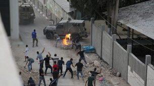محتجون يلقون الحجارة والزجاجات الحارقة باتجاه القوات الإسرائيلية في قرية شويكة في الضفة الغربية، بلدة مسلح فلسطيني قتل إسرائيليين اثنين في المنطقة الصناعية بركان في 7 أكتوبر، 2018. ( AFP PHOTO / JAAFAR ASHTIYEH)