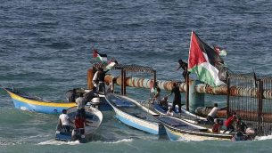متظاهرون فلسطينيون على متن قوارب يرفعون الاعلام الفلسطينية على مبنى حديدي عند الحدود البحرية مع اسرائيل، في شمال قطاع غزة، 8 اكتوبر 2018 (AFP PHOTO / Said KHATIB)