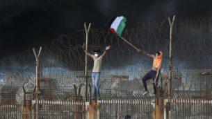 متظاهرون فلسطينيون يرفعون علم فلسطيني على مبنى حديدي خلال مظاهرة في شاطئ بالقرب من الحدود البحرية مع اسرائيل، في شمال قطاع غزة، 8 اكتوبر 2018 (Said KHATIB / AFP)