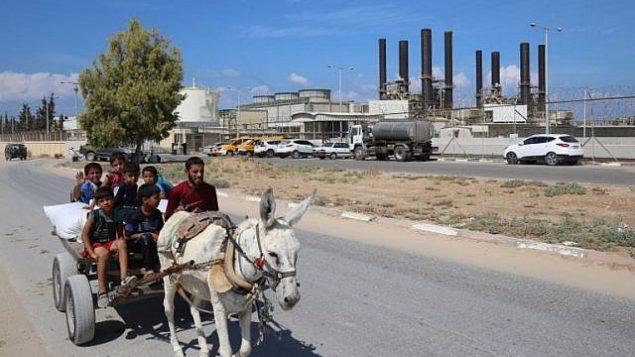 فلسطييون يركبون عربة مربوطة بحمار بالقرب من محطة الكهبراء في النصيرات، في وسط قطاع غزة، 9 أكتوبر، 2018. (AFP/Said Khatib)