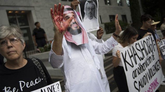 متظاهرا مرتديا قناع بشكل وجه ولي العهد السعودي محمد بن سلمان مع ايدي ملطخة بالدماء، في احتجاج امام السفارة السعودية في واشنطن، مطالبة بالعدالة للصحفي السعودي المفقود جماش خاشقجي، 8 اكتوبر 2018 (Jim Watson/AFP)