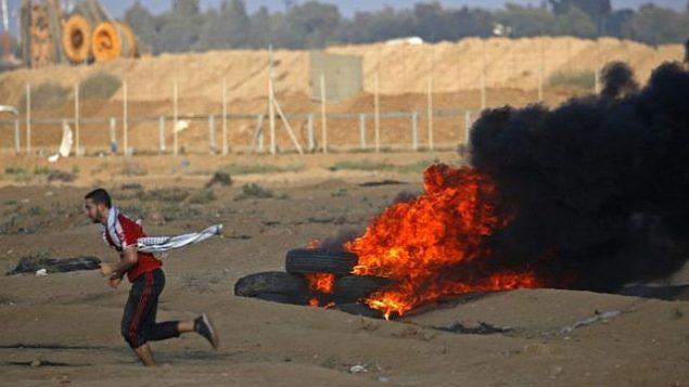 محتج فلسطيني يركض بجانب إطارات محترقة على الحدود بين إسرائيل وغزة، شرق مدينة غزة، في 12 أكتوبر 2018. (Said KHATIB / AFP)