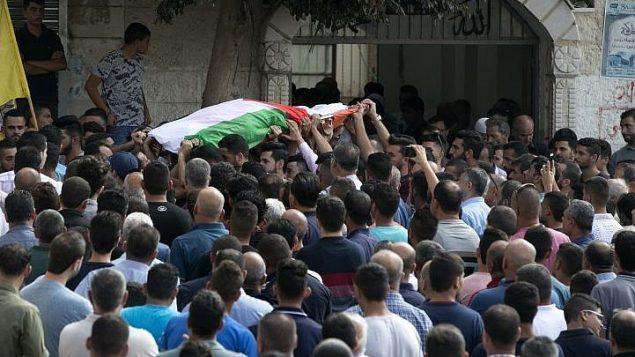 فلسطينيون يشيعون جثمان عائشة الرابي (48 عاما) ، التي توفيت متأثرة بجراحها نتيجة هجوم رشق حجارة تعرضت اليه مع زوجها خلال سفرهم بسيارة، في قرية بديا في الضفة الغربية، 13 اكتوبر 2018 (JAAFAR ASHTIYEH / AFP)