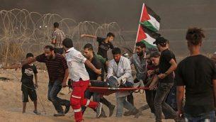 مسعفون فلسطينيون يحملون متظاهر مصاب خلال تظاهرة بالقرب من الحدود مع إسرائيل، شرق مدينة غزة، في 19 أكتوبر 2018. (MAHMUD HAMS / AFP)