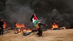امرأة فلسطينية ترفع العلم الفلسطيني وسط دخان أسود من الإطارات التي أحرقها المتظاهرون، خلال اشتباكات قرب الحدود مع إسرائيل شرق مدينة غزة في 26 أكتوبر 2018. (MAHMUD HAMS / AFP)