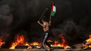 متظاهر يحمل العلم الفلسطيني بينما يستخدم مقلاع لرشق الحجارة باتجاه جنود اسرائيلبيين خلال اشتباكات بالقرب من الحدود مع اسرائيل، شرقي مدينة غزة، 26 اكتوبر 2018 (Mahmud Hams/AFP)