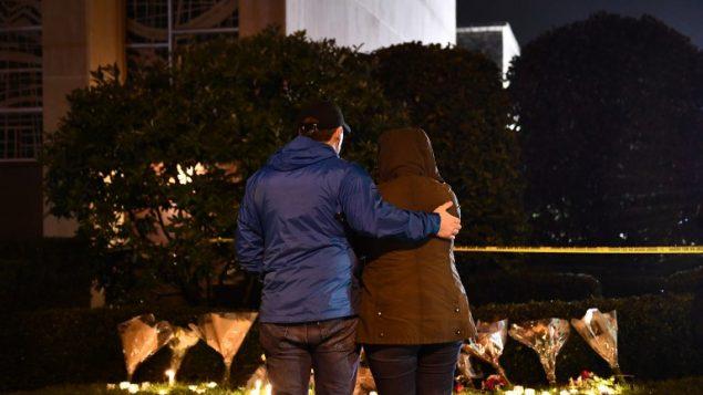 اشخاص يقفون امام شموع مضاءة خارج كنيس 'شجرة الحياة' بعد هجوم اطلاق نار راح ضحيته 11 شخصا في بتسبورغ، 27 اكتوبر 2018 (Brendan Smialowski / AFP)