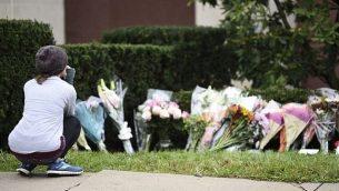 في اليوم التالي لإطلاق نار مميت، تنظر امرأة إلى الزهور كجزء من نصب تذكاري خارج كنيس شجرة الحياة، في 28 أكتوبر، 2018. (Brendan SMIALOWSKI / AFP)