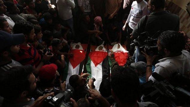 مشيعون يحملون جثامين ملفوفة بالأعلام الفلسطينية لثلاثية فتية قُتلوا في غارة جوية إسرائيلية، خلال جنازتهم في مدينة دير البلح، وسط قطا ع غزة، 29 أكتوبر، 2018. (MAHMUD HAMS / AFP)
