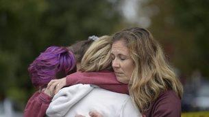 من اليسار: كودي مورفي، 17 عاما، سابرينا ويهراوخ، و أماندا غودلي، جميعهم في بيتسبيرغ، يتعانقون بعد وضع الهجوم في كنيس شجرة الحياة يوم السبت، 27 أكتوبر ، 2018. (Andrew Stein/Pittsburgh Post-Gazette via AP)