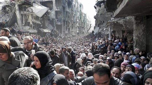 ملف - في 31 كانون الثاني / يناير 2014، تظهر صورة الملف الصادرة عن الأونروا، سكان مخيم اليرموك الفلسطيني المحاصر، يصطفون للحصول على الإمدادات الغذائية، في دمشق، سوريا (UNRWA via AP, File)