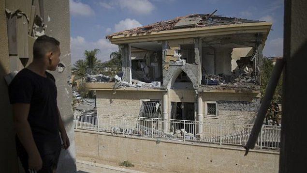 رجل يشاهد منزلا أصيب بصاروخ أطلق من قطاع غزة، في مدينة بئر السبع، جنوب إسرائيل، الأربعاء، 17 أكتوبر، 2018. (AP/Tsafrir Abayov)